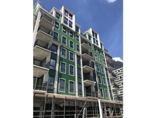 een-dynamisch-gevelbeeld-met-groene-beplating-karakteristieke-balkons-witte-pandsgewijze-omlijstingen-en-hoekige-halsgevels.-kopieren